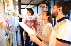 Tres empresarios que discuten y que planean concepto Frente del marcador y de las etiquetas engomadas de la pared de cristal imagen de archivo libre de regalías