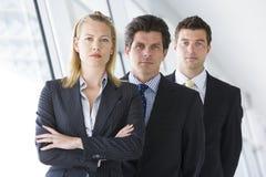 Tres empresarios que se colocan en pasillo Imagenes de archivo