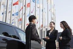 Tres empresarios que se encuentran al aire libre con las astas de bandera en fondo. Imagen de archivo