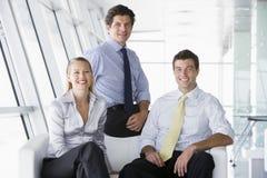 Tres empresarios que se sientan en pasillo de la oficina Imagen de archivo libre de regalías