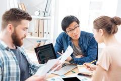 Tres empresarios que se sientan y que trabajan en oficina junto fotografía de archivo libre de regalías