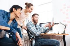 Tres empresarios que trabajan con la tableta en oficina fotos de archivo