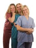Tres enfermeras en médico friegan la ropa Imágenes de archivo libres de regalías