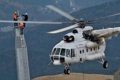 Tres ensambladores que golpean pesadamente debajo del helicóptero Imagen de archivo libre de regalías