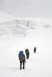 Tres escaladores en el glaciar imagenes de archivo