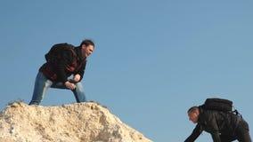 tres escaladores suben uno tras otro en la roca blanca Trabajo en equipo de hombres de negocios los turistas dan la mano el uno a almacen de metraje de vídeo