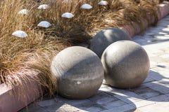 Tres esferas concretas grandes en el fondo de la hierba amarilla, del parque moderno y del diseño del jardín fotografía de archivo libre de regalías