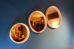 Tres espejos formados círculo de lado a lado en la pared foto de archivo libre de regalías