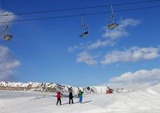 Tres esquiadores en cuesta en el día agradable del sol Imagen de archivo libre de regalías
