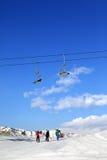 Tres esquiadores en cuesta en el día de invierno del sol Fotos de archivo libres de regalías