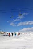 Tres esquiadores en cuesta en el día del sol Imagen de archivo