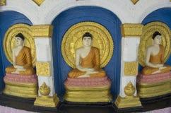 Tres estatuas budistas hermosas en el altar en el templo imagenes de archivo