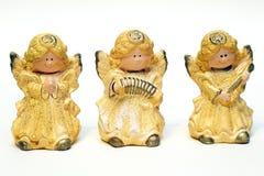 Tres estatuillas de cerámica de ángeles amarillean en un fondo blanco fotos de archivo