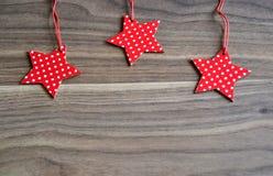 Tres estrellas rojas en fondo de madera Imagen de archivo