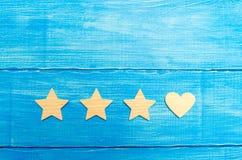 Tres estrellas y un corazón en un fondo azul Selección del usuario y de los clientes Reconocimiento y admiración universales Grad imagenes de archivo