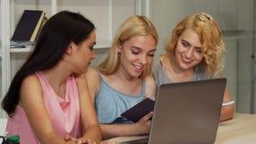 Tres estudiantes alegres que leen un libro junto fotografía de archivo libre de regalías