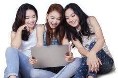 Tres estudiantes con el ordenador portátil en el piso Imágenes de archivo libres de regalías