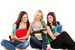 Tres estudiantes con los cuadernos que se sientan junto encendido Imágenes de archivo libres de regalías