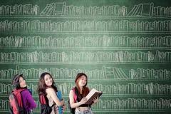 Tres estudiantes con los libros en la pizarra Fotos de archivo