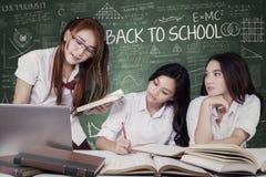 Tres estudiantes de nuevo a escuela y el estudiar en clase Imagenes de archivo