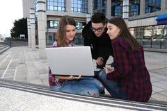 Tres estudiantes del adolescente con el ordenador portátil Fotos de archivo libres de regalías