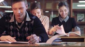 Tres estudiantes en biblioteca de universidad que estudian sus libros y que gozan de ellos metrajes
