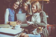 Tres estudiantes en café usando la tableta y la ha digitales fotografía de archivo libre de regalías