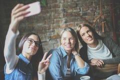 Tres estudiantes en el café que toma la imagen del uno mismo fotografía de archivo libre de regalías