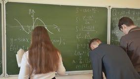 Tres estudiantes escriben en las fórmulas matemáticas de la pizarra en la sala de clase Escuela rusa metrajes