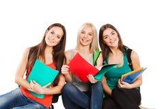 Tres estudiantes felices que se sientan así como la diversión Fotografía de archivo libre de regalías