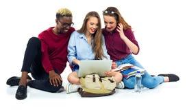 Tres estudiantes felices que se sientan con los libros, el ordenador portátil y los bolsos Fotografía de archivo