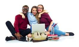Tres estudiantes felices que se sientan con los libros, el ordenador portátil y los bolsos Foto de archivo
