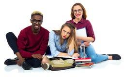 Tres estudiantes felices que se sientan con los libros, el ordenador portátil y los bolsos Imagen de archivo
