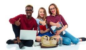 Tres estudiantes jovenes felices del adolescente con los pulgares para arriba aislados en w Foto de archivo libre de regalías