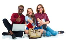 Tres estudiantes jovenes felices del adolescente con los pulgares para arriba aislados en w Imagen de archivo