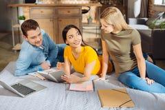 Tres estudiantes pensativos alegres que realizan tarea imagenes de archivo