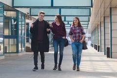 Tres estudiantes que caminan y que sonríen foto de archivo
