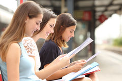 Tres estudiantes que estudian y que aprenden en una estación de tren Fotografía de archivo libre de regalías