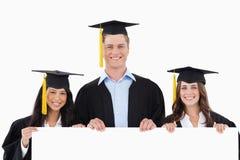 Tres estudiantes que gradúan sosteniendo un cartel en blanco Imágenes de archivo libres de regalías