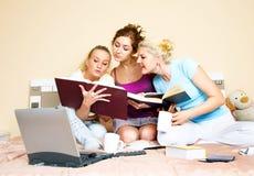 Tres estudiantes que leen un libro Imagen de archivo