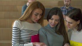 Tres estudiantes que miran el diario ilustrado almacen de metraje de vídeo