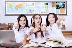 Tres estudiantes que muestran los pulgares para arriba Fotos de archivo