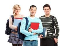 Tres estudiantes que presentan con los libros Foto de archivo