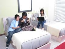 Tres estudiantes que se relajan en la cama con la computadora portátil Imágenes de archivo libres de regalías