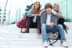 Tres estudiantes que se sientan afuera Foto de archivo libre de regalías