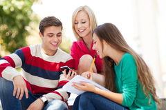 Tres estudiantes que se sientan junto Imágenes de archivo libres de regalías