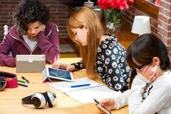 Tres estudiantes que trabajan en los dispositivos digitales. Imagenes de archivo