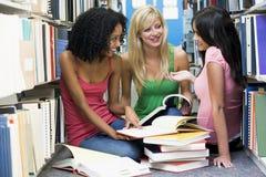 Tres estudiantes que trabajan junto en biblioteca Imágenes de archivo libres de regalías