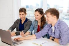 Tres estudiantes sonrientes con el ordenador portátil y los cuadernos Imagen de archivo libre de regalías