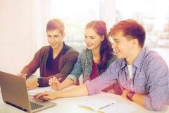 Tres estudiantes sonrientes con el ordenador portátil y los cuadernos Imágenes de archivo libres de regalías